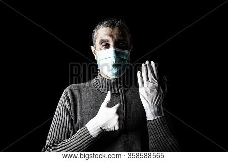 Man with surgical mask, protective gloves and thumbs up. Pandemic or epidemic and scary, fear or danger concept. Protection for biohazard like COVID-19, Coronavirus, Ebola. Black Background
