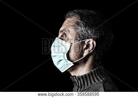 Man with surgical mask. Pandemic or epidemic and scary, fear or danger concept. Protection for biohazard like COVID-19 aka Coronavirus. Profile portrait. Black Background