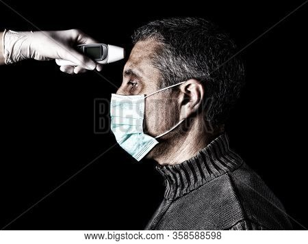 man having the fever measured or taken with digital thermometer by nurse. Pandemic or epidemic and scary, fear or danger concept. Protection for biohazard like COVID-19 aka Coronavirus