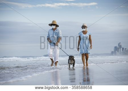 A Couple With Medical Masks Walking An English Blue Staffy Dog, Seaside On A Beautiful Beach. Walkin