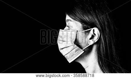 Woman with surgical mask. Pandemic or epidemic and scary, fear or danger concept. Protection for biohazard like COVID-19 aka Coronavirus. Close-up profile  portrait. Black Background. Black and White
