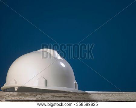 Safety first concept white hard safety wear helmet hat - Engineer worker helmet on blue background.