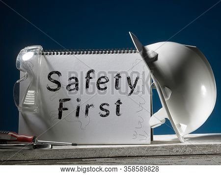 Safety first concept white hard safety wear helmet hat with drawing pad