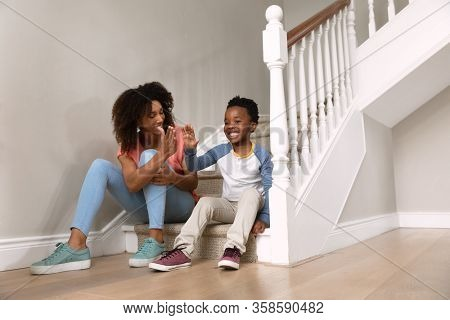 Front view of an African American woman with her son at home, sitting on stairs giving a high five. Family enjoying time at home, lifestyle concept