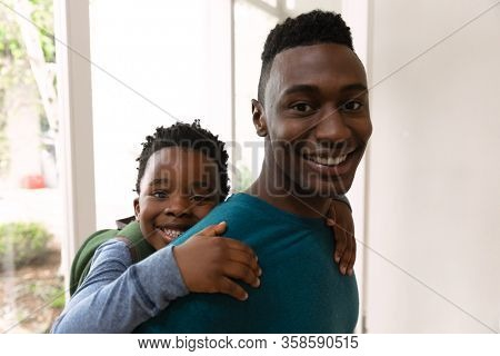 Portrait of a happy African American man at home carrying his son piggyback and smiling to camera. Family enjoying time at home, lifestyle concept