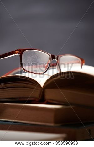 Stack Of Books With Eyeglasses At Classroom Against Blackboard