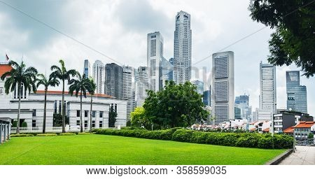 Modern Skyline Of Singapore City, Urban Asian Cityscape With Skyscraper Buildings And Green Grass Fi