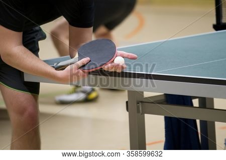 table tennis player doing a serve, close-up
