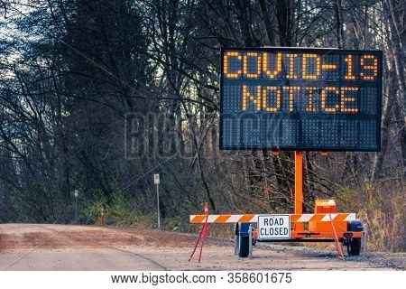 Large Electronic Notification Sign On Rural Street Announcing Road Closure Due To Coronavirus Covid-