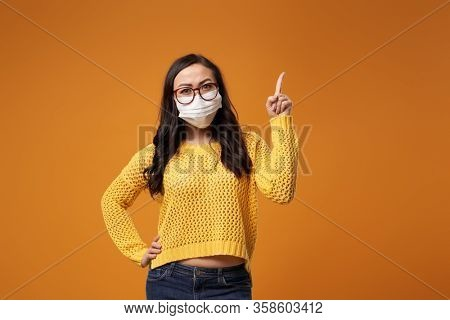 Chine woman with glasses and medical mask pointing hand up in studio