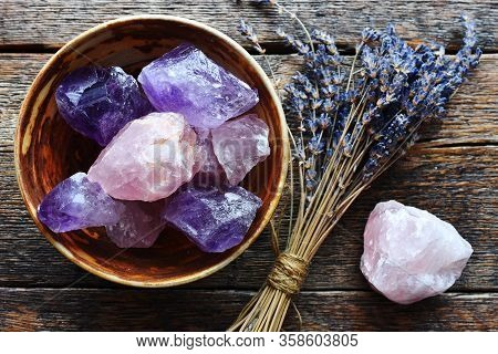 A Table Top Image Of A Pottery Bowl With Large Rose Quartz And Amethyst Crystal With Dried Lavender