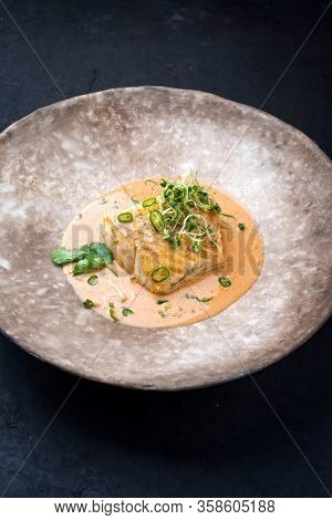 Gourmet fried skrei cod fish in Thai curry with chili and sprouts as closeup on a modern design plate with copy space