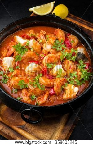 Traditional American fish stew cioppino with prawns, and fish as closeup in a modern design cast-iron roasting dish