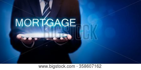 Real Estate Agents Offer The Word Mortgage. Property Mortgage Concept. Businessman Is Showing The Wo