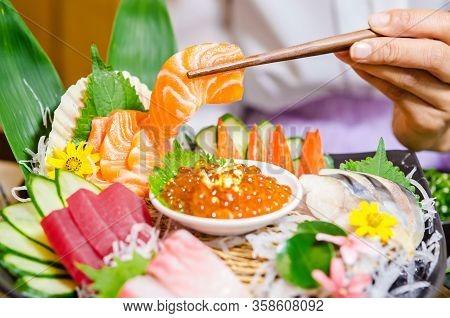 Salmon Sashimi In Chopsticks On Sashimi Set Table In Japanese Restaurant.