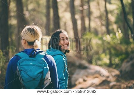 Two Girls With Backpacks Walk In The Woods. Hiking In The Mountains. Girlfriends Spend Time Together