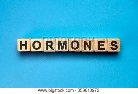 Hormones Word Cube On A Blue Background. Medical Concept.