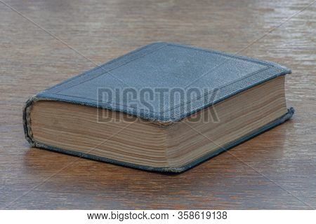 An Old Shabby Book Lies On An Old Shabby Wooden Table. Close-up. Warm Colors.