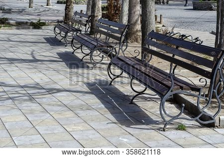 Empty Benches In A City Square. A Row Of Empty Street Benches In A Spring Sunny City. Warm Spring Da