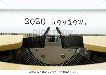2020 Review Word Typed On A Yellow Vintage Typewriter. Business Concept.