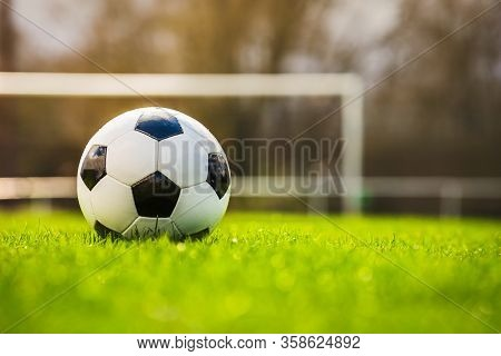 Classic Soccer Ball In Sunset  With Typical Black And White Pattern, Placed On Stadium Turf. Traditi