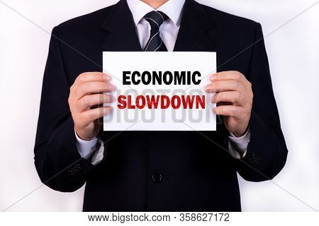 A Businessman Is Holding A Tablet With The Text Economic Slowdown In Front Of Him In His Hands. Busi