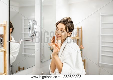 Young Woman In Bathrobe Taking Care Of Her Skin, Looking At The Mirror In The Bathroom. Facial Skin