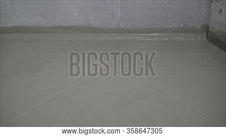 A Worker Is Waterproofing A Concrete Floor. Construction Mix Waterproofing. Concrete Floor With Fres