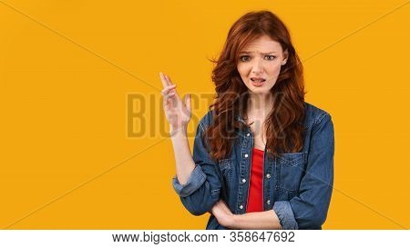 Discontented Girl Gesturing With Hand Looking At Camera Disapproving Something Standing Over Yellow