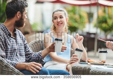 Pretty Smiling Young Woman Drinking Coffee And Discussing Plans And Ideas With Business Partners Ta