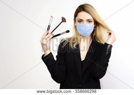 Attractive Blonde Make-up Artist In Mask Holding Brushes On White Background, Coronavirus Outbreak D