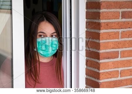 young woamn wearing medical mask confined at home. Coronavirus concept