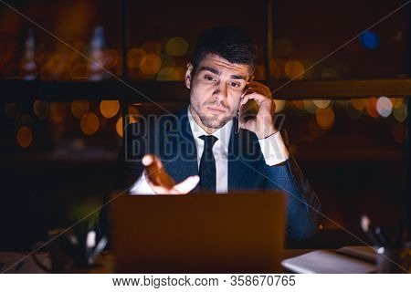Discontented Businessman Talking On Mobile Phone Having Problem With Laptop Computer Sitting In Mode