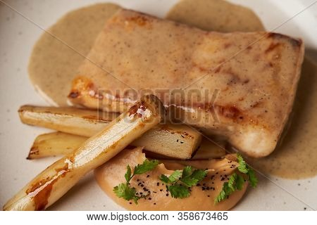 Baked Sturgeon Fillet With Spinach On A White Plate On Gray Table