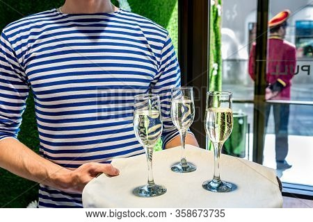 Man Waiter In Striped Vest Welcomes Guests With Glasses Of Champagne On The Event