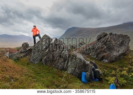 Female Tourist On A Halt Stands On A Stone Eating Chocolate And Looks Into The Distance. Sarek