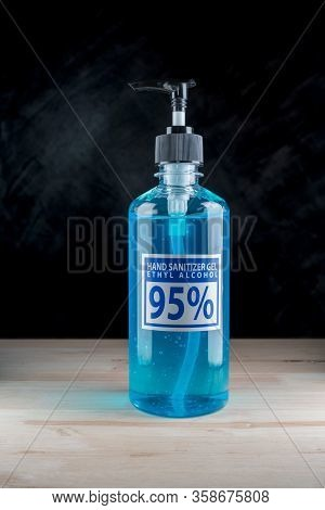 Bottle Of Hand Sanitizer Blue Gel With Ingredient Ethyl Alcohol 95% On Wooden Table With Dark Backgr