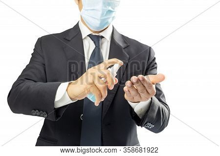 Businessman Wearing Medical Face Mask And Desinfecting Hands With Alcohol Spray Isolated
