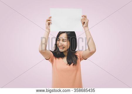Asian Pretty Woman Showing Blank White Paper For Copy Space And Message With Happy And Smile In Conc