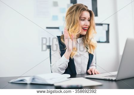 Young Beautiful Businesswoman Manager With Red Lipstick Works In Her Modern Office, Waving During On