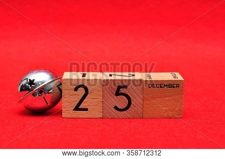 25 December On Wooden Blocks With A Silver Bell On A Red Background
