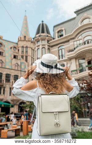 Stylish Female Girl In White Dress Discovering And Searching Famous Places, Traveling Alone In Europ