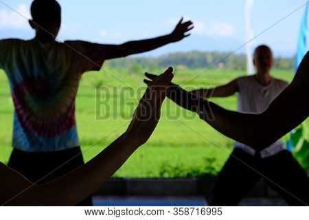 Hands Of People In The Shade Engaged In The Practice Of Self-healing With Qigong Energy With A Direc