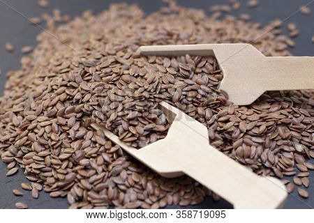 Pile Of Flax Or Flax Seeds In A Wooden Spoon On A Black Stone Background. Dark Background Flaxseed C