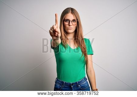 Young beautiful redhead woman wearing casual green t-shirt and glasses over white background Pointing with finger up and angry expression, showing no gesture