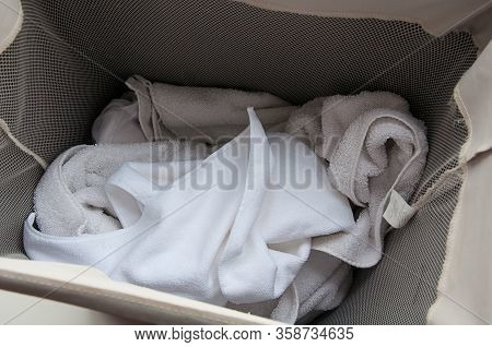 Dirty Laundry Of Mostly Towels In A Laundry Hamper Closeup.  Concepts Of Clean, Cleanliness, And Wor