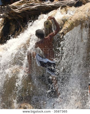 Man Climbing Up A Waterfall