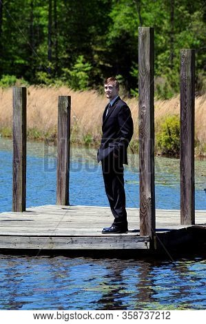Tall And Slender, Young Man Stands On Wooden Dock In South Arkansas.  He Is Wearing A Black Business