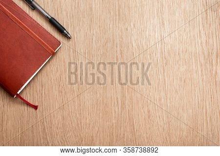 Brown Notebook And Black Pen On A Wooden Surface. Business Concept. Business People Items. Free Spac