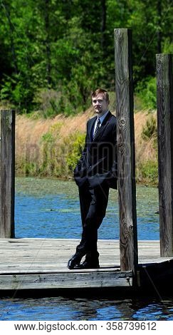 Handsome Young Man Leans Against A Rustic Wooden Post.  He Is Standing On A Dock In A Dressy Busines